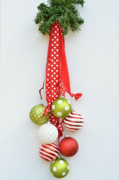 Create a door hanging with ribbon and Christmas ornaments.