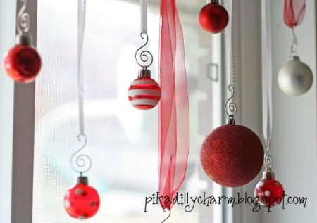 hang christmas ornaments from ribbon in front of a window